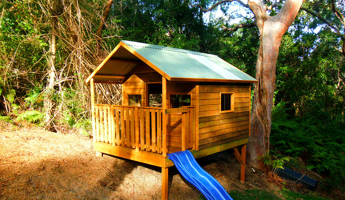 large outdoor wooden cubby with slide