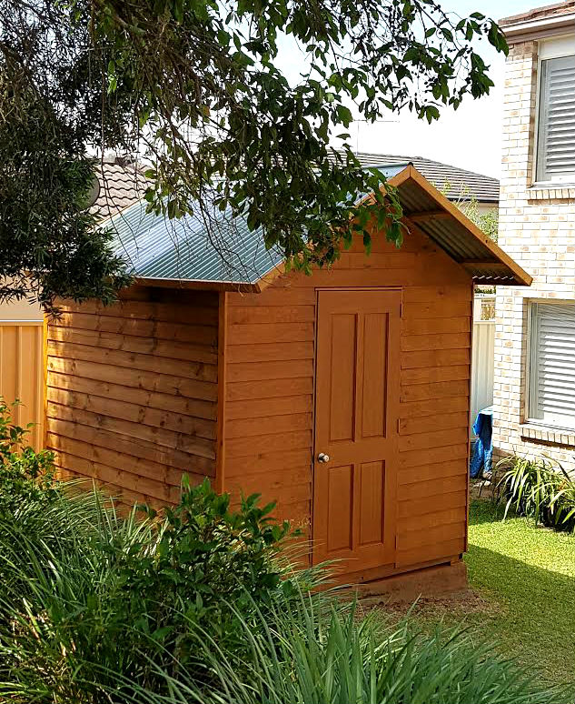 small timber shed stained in deep cedar color