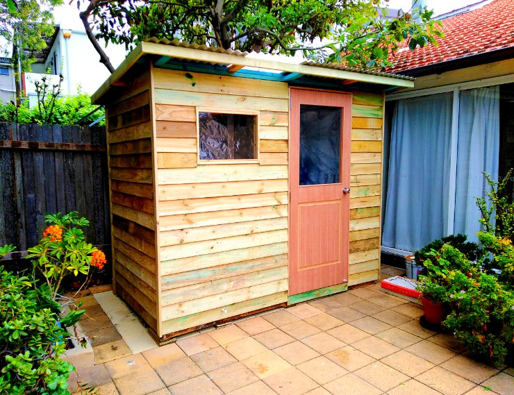small back garden shed with windows in front wall and door