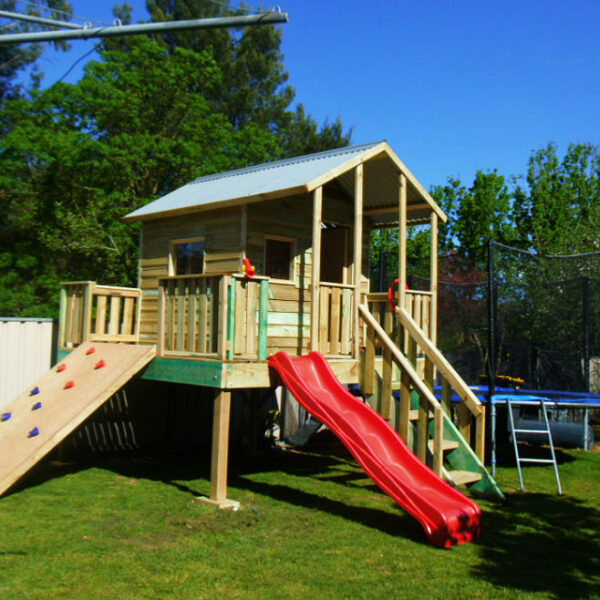 elevated cubby house with two sides sheltered verandah includes red slide and adjustable rock climbing wall