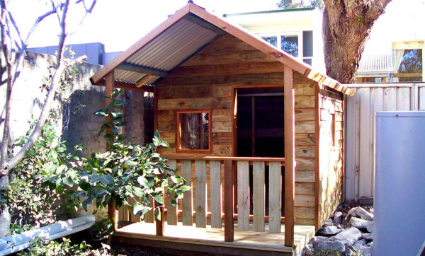small themed wooden cubby with verandah 2.2m x 1.8m, two perspex windows, stained trim $1850 with accessories as shown
